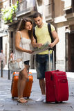 Couple with luggage reading map Royalty Free Stock Photo
