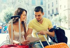 Couple with luggage reading map. Man with smiling girlfriend reading the map at street with luggage Royalty Free Stock Photos