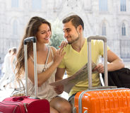 Couple with luggage reading map Stock Photos