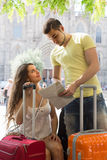 Couple with luggage reading map Royalty Free Stock Photos