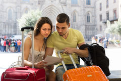 Couple with luggage reading map. Two friends with luggage reading the map at street Royalty Free Stock Image