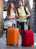 Couple with luggage reading map Stock Images