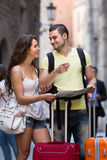 Couple with luggage reading map Stock Photography