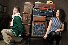 Couple and luggage. Young couple on a cart with a bunch of old suitcases royalty free stock photos