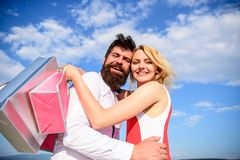 Couple with luxury bags hugs blue sky background. Happy couple luxury purchases. Man beard and girl enjoy shopping. Together. Family bought excellent clothes royalty free stock image