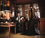 Couple in luxury interior. Elegant couple in formal dress in luxury cabinet Stock Photos