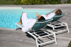 Couple in luxury resort relaxing by swimming pool Royalty Free Stock Image