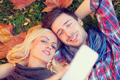 Couple lying on autumn leaves make a Selfie Royalty Free Stock Photography