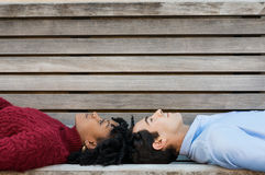 Couple lying on back and thinking. Young couple lying on bench head to head. African women and young men looking up, lying on bench. Pensive couple lying on back Stock Photography
