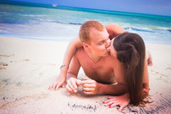 Couple lying on the beach Stock Photos