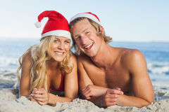 Couple lying on beach wearing christmas hats Royalty Free Stock Photography