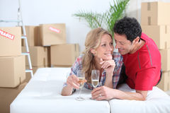 Couple lying on bed. Celebrating moving into new home stock image