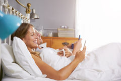 Couple Lying In Bed Checking Mobile Phones Stock Photos