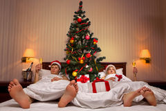 Couple lying on bed with Christmas tree Stock Photos