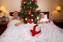 Couple lying on bed with Christmas tree Stock Photo