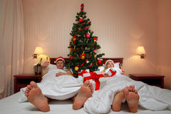 Couple lying on bed with Christmas tree Royalty Free Stock Images