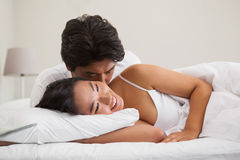 Couple lying in bed and cuddling Stock Photos