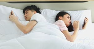 Couple lying in bed facing in opposite directions.