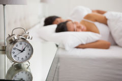 Couple lying in bed with focus on alarm clock Royalty Free Stock Image
