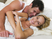 Couple lying in bed laughing stock photos