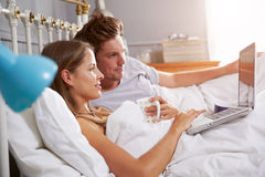Couple Lying In Bed Looking At Laptop Royalty Free Stock Image