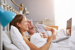 Couple Lying In Bed Looking At Laptop Royalty Free Stock Photos