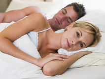 Couple lying in bed with the man sleeping Royalty Free Stock Photos