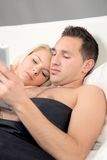 Couple lying in bed reading a tablet-pc Royalty Free Stock Photos