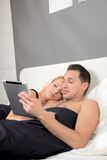Couple lying in bed reading a tablet-pc Royalty Free Stock Image