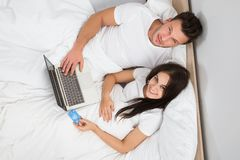 Couple lying on bed shopping online Royalty Free Stock Images