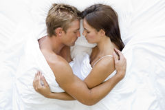 Couple lying in bed sleeping stock images