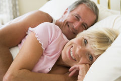 Couple lying in bed smiling stock image