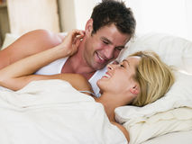 Couple lying in bed smiling Royalty Free Stock Photo
