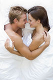 Couple lying in bed smiling. Arms around one another royalty free stock photography