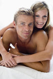 Couple lying in bed smiling Stock Photography