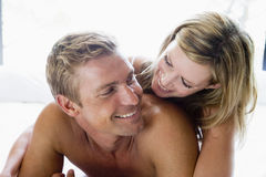 Couple lying in bed smiling Royalty Free Stock Photos