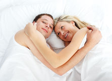 Couple lying in bed and smiling at the camera Stock Photos