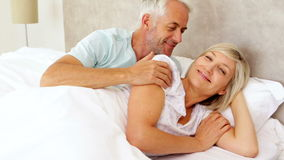 Couple lying in bed and smiling at camera