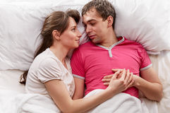 Couple lying in bed smiling Stock Images