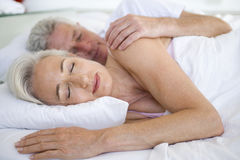 Couple lying in bed together sleeping Royalty Free Stock Images