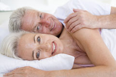 Couple lying in bed together smiling Royalty Free Stock Photos
