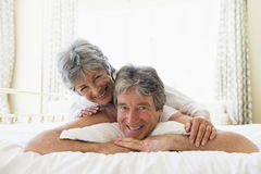 Couple lying on bed together smiling Royalty Free Stock Image