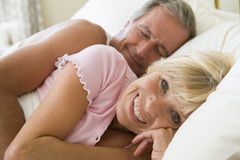 Couple lying in bed together smiling Royalty Free Stock Images