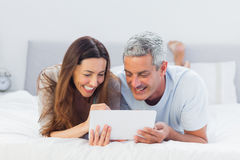 Couple lying on bed using their tablet pc Stock Images