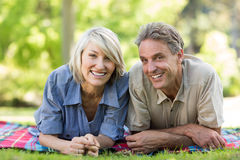 Couple lying on blanket in park Stock Images