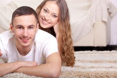 Couple lying on carpet Stock Images