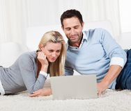 Couple lying on a carpet with a laptop Stock Photo