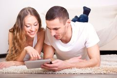 Couple lying on carpet and looking at tablet Stock Photo