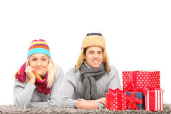 Couple lying on a carpet near presents Royalty Free Stock Photos