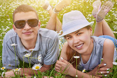 Couple lying on chamomile meadow Royalty Free Stock Images